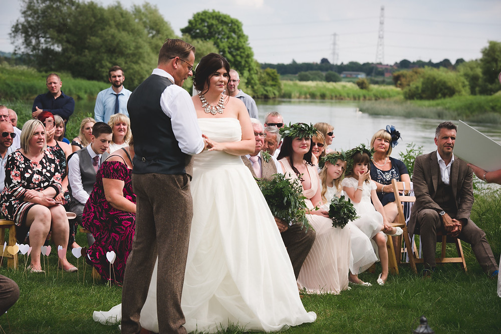 Swan swimmig past on River Trent at end of outdoor wedding ceremony at Swarkestone Pavilion