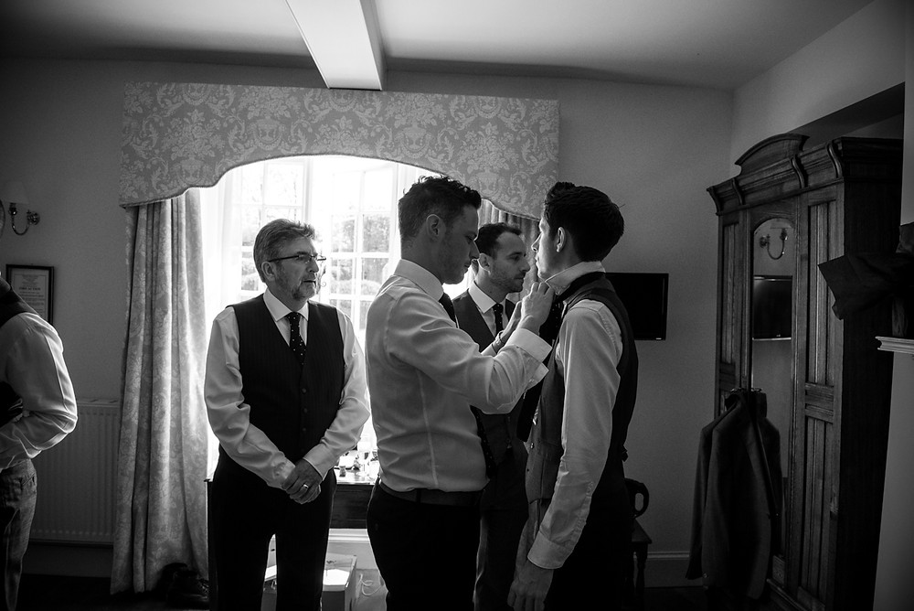 Groomsman doing up tie for groom at Wethele Manor wedding