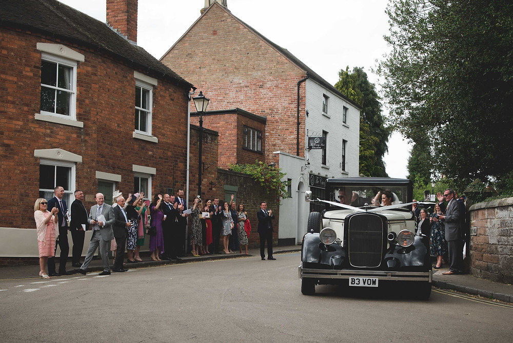 guests lined up in the street in Brewood to wave of the newlyweds