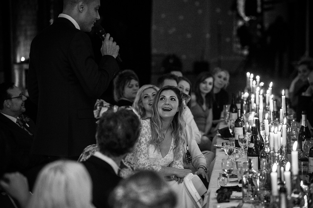 bride at bristol paintworks wedding looking at her husband during his speech