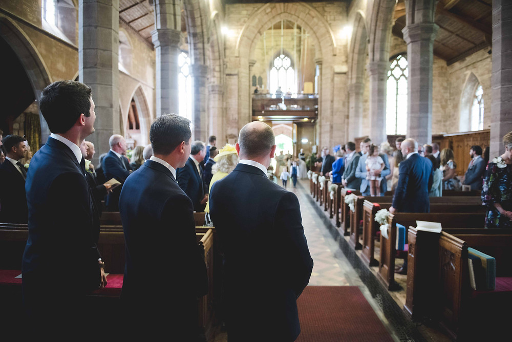 Groom waiting for bride to arrive at St Mark's church in Staffordshire