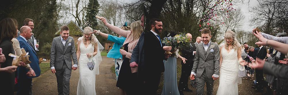 Happy Bride & Groom getting confetti thrown over them