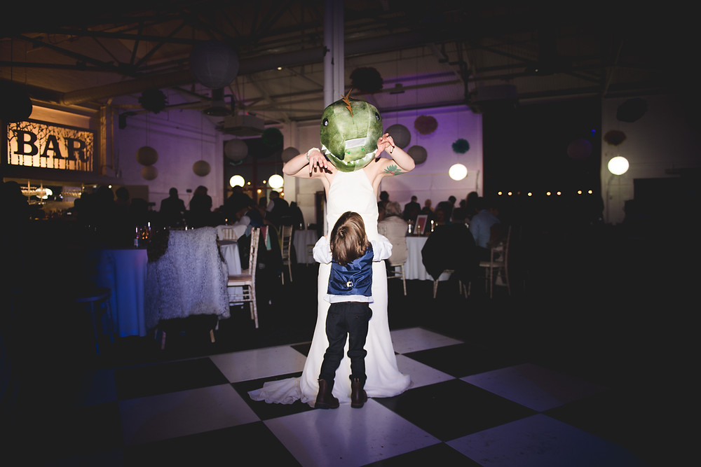 Quirky photo of the bride, wearing a lizards head on the dancefloor at The Bond Company in Digbeth