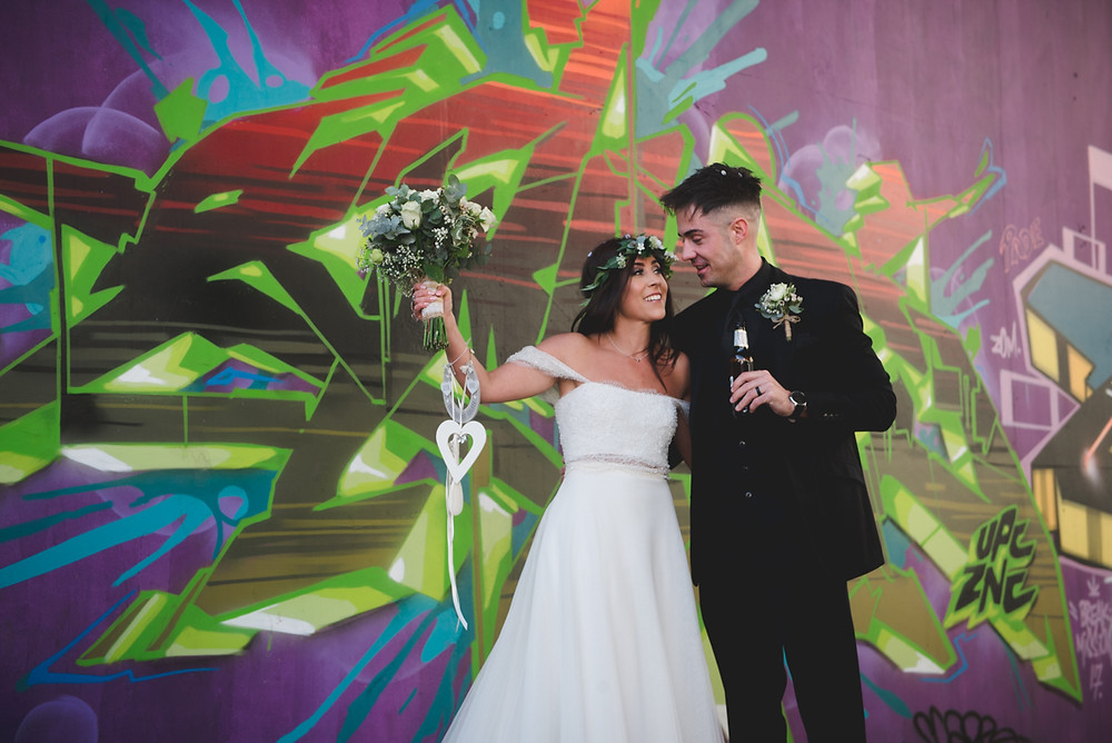bride & groom in front of some graffiti in centra lbirmingham