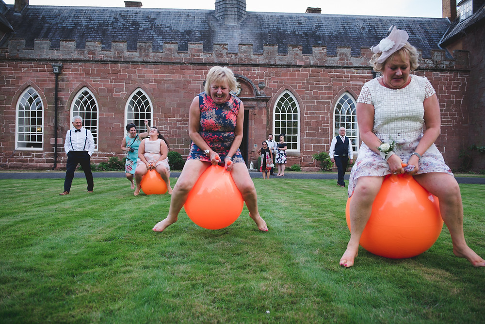 Hartlebury Castle wedding guests having space hopper races