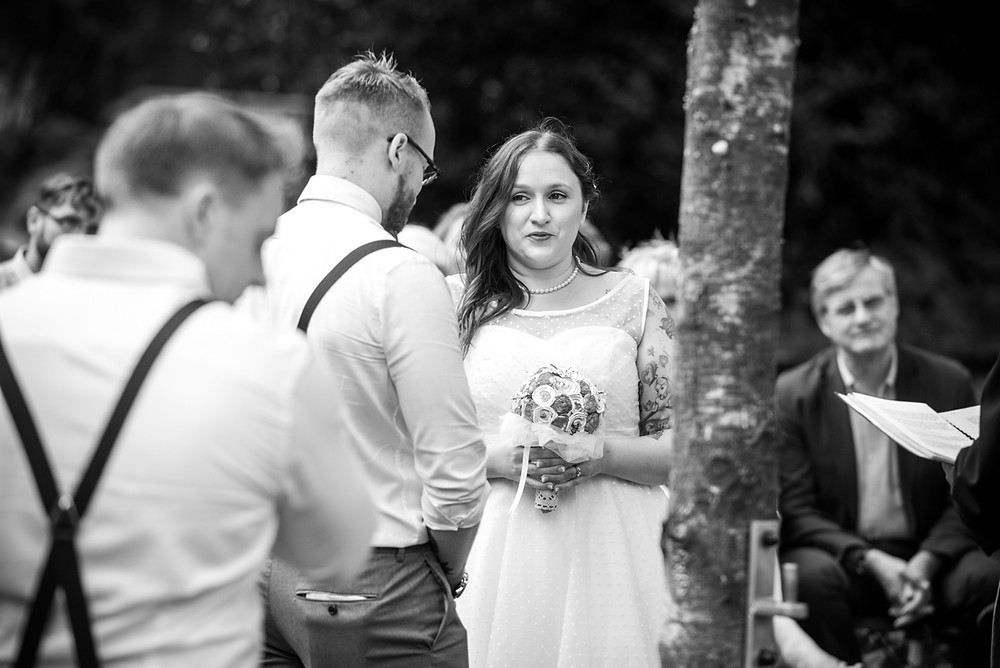 black & white wedding photograph of bride & groom during open air wedding ceremony