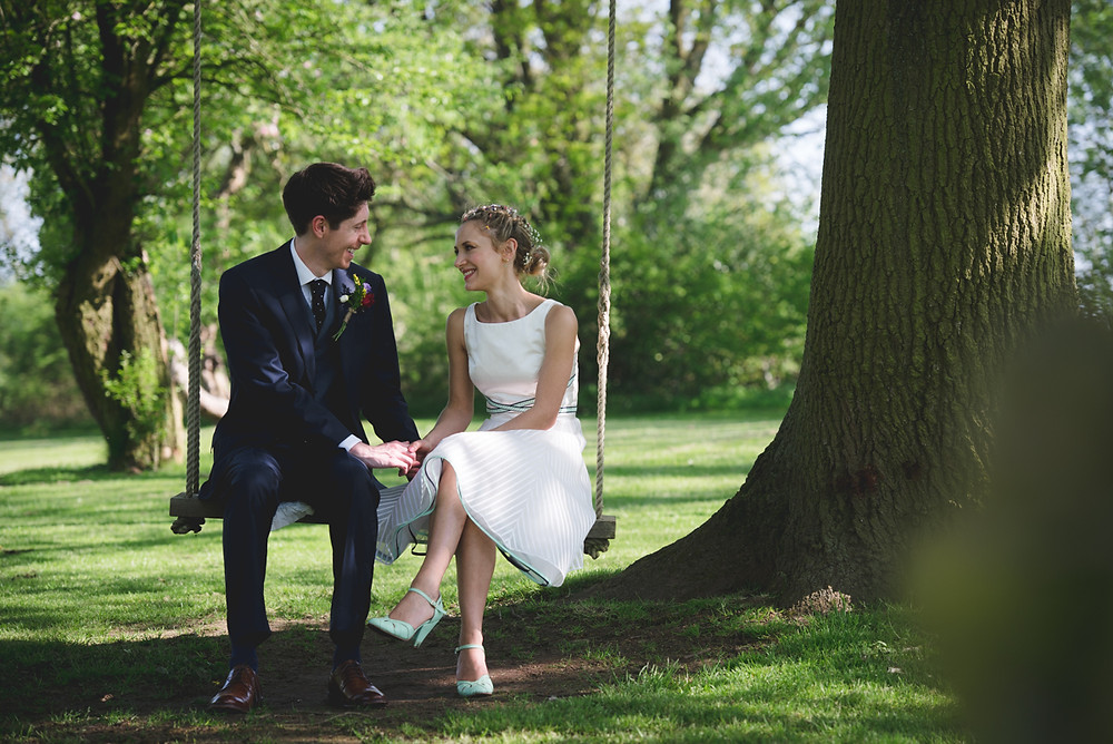 Newly married Bride & Groom sitting on a swing at their Leamington Spa outside wedding