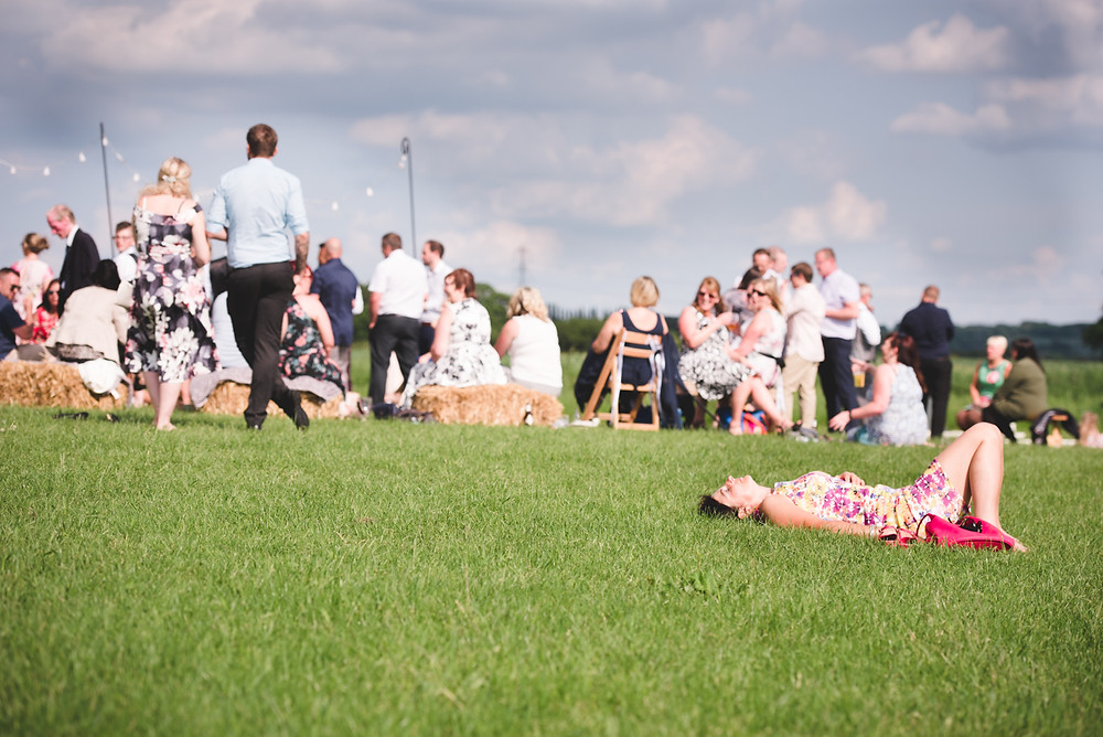 Wedding guest asleep on the grass as other guests drink and chat behind her