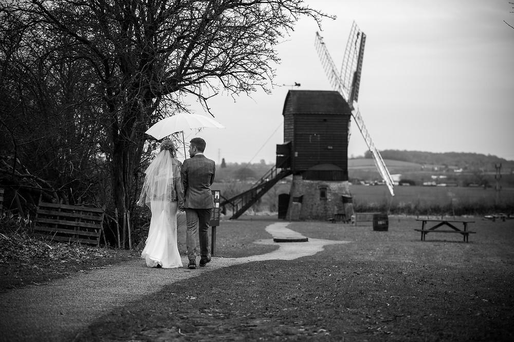 Newlyweds walking towards windmill at Avoncroft Museum
