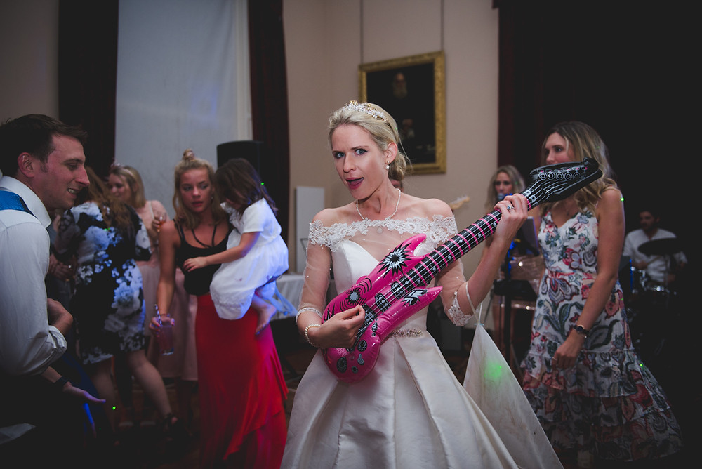 Bride playing an inflatable guitar on dancefloor at Whitbourne Hall wedding reception