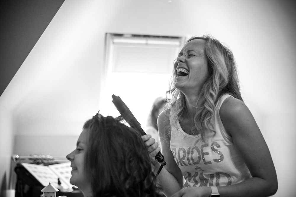 Bridesmaid laughing as she does her friends hair