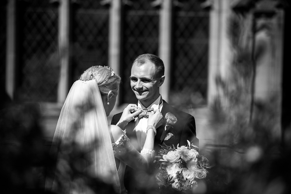 Bride adjusting grooms bow tie after their Worcester Cathedral wedding