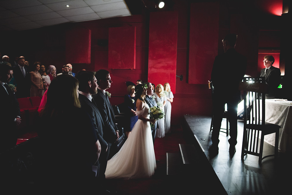 side view of bride and her father, just about to walk up on the stage for her wedding at the electric cinema