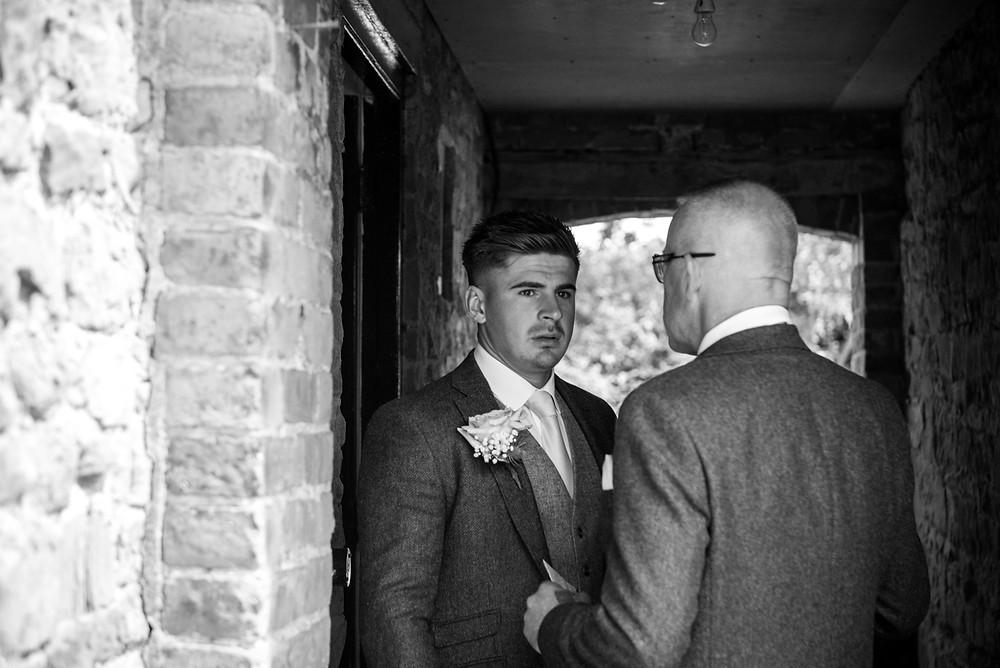 Pensive looking groom at Delbury Hall wedding