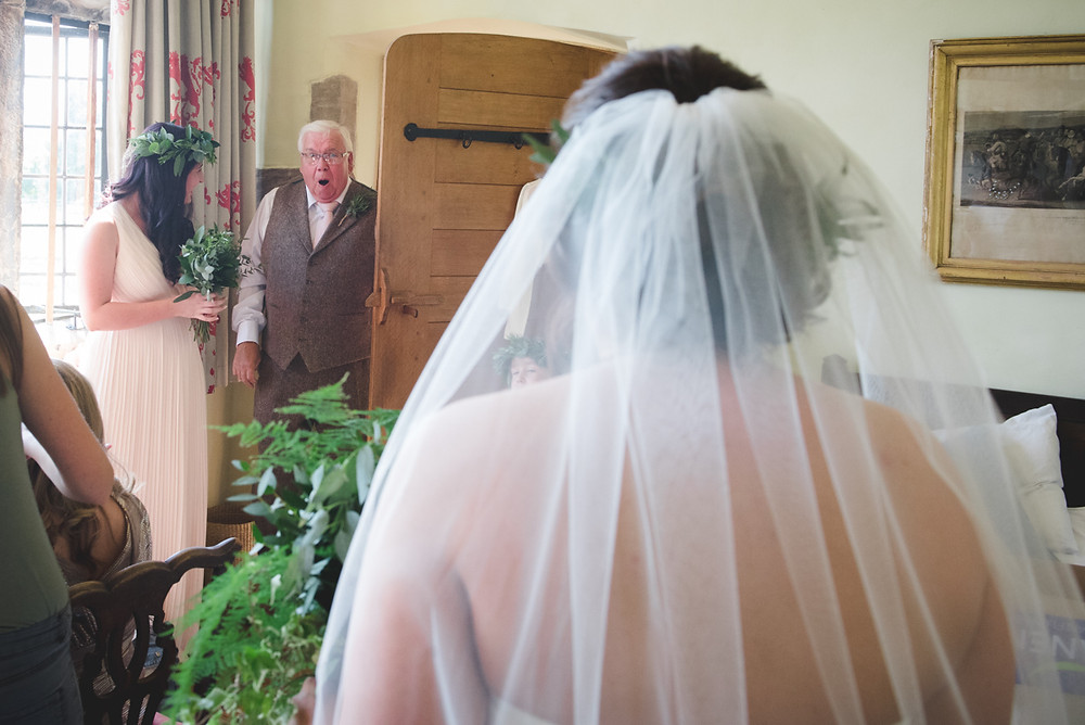 Father of the bride open mouthed as he sees her for the first time in her dress at Swarkestone Pavilion