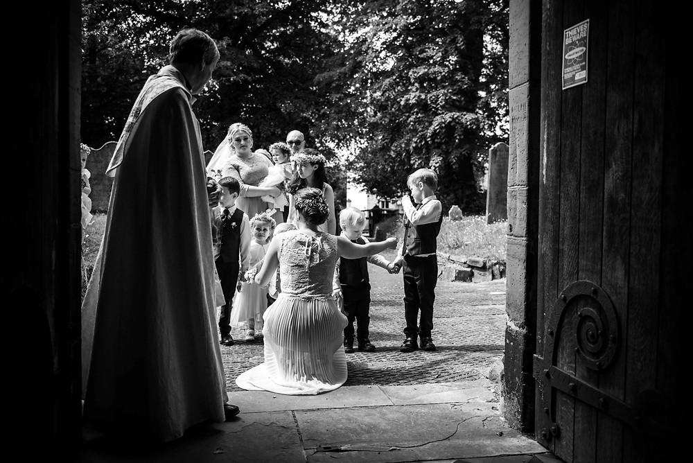 Black & white wedding photo outside St Mark's church in Brewood
