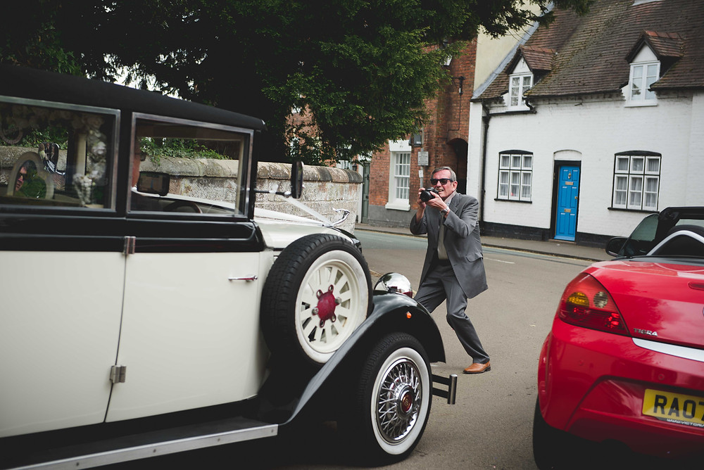guest standing in the road to photograph the wedding car in Brewood