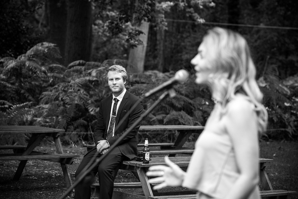 Natural black & white photograph of wedding singer in the woods