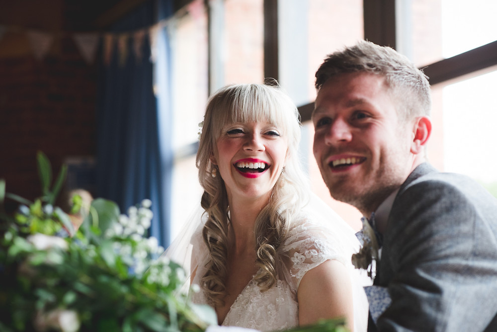Relaxed, candid photograph of laughing bride & groom as they sign the register