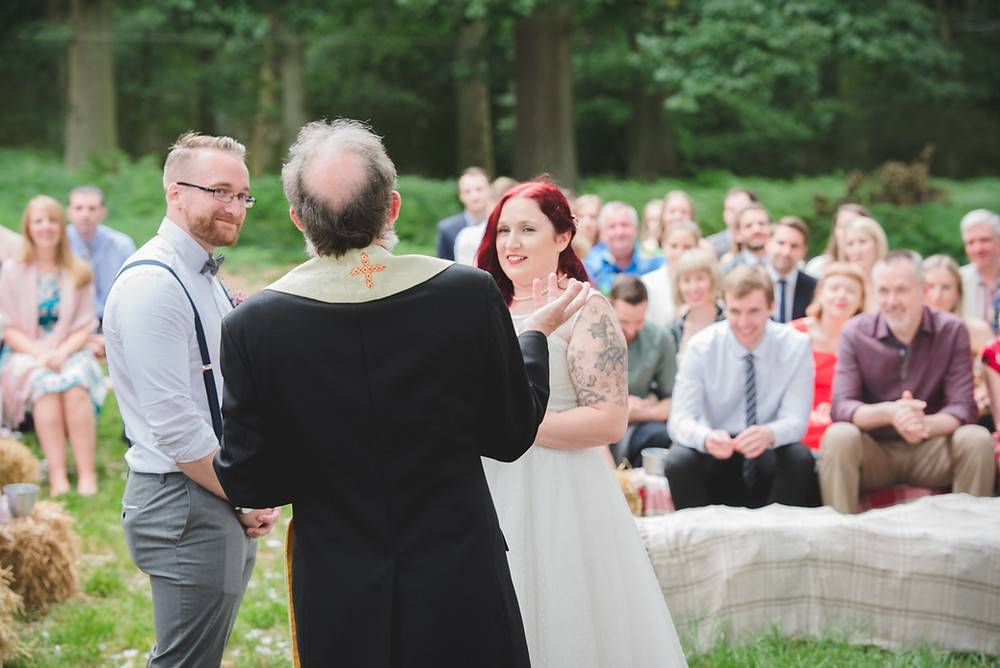 Natural photograph of vicar conducting open air wedding in Warwickshire