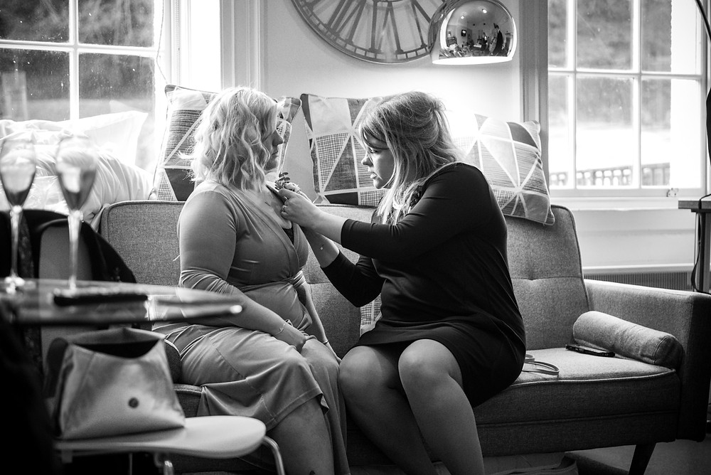 Bridesmaids helping each other to put button holes on -black & white wedding photograph