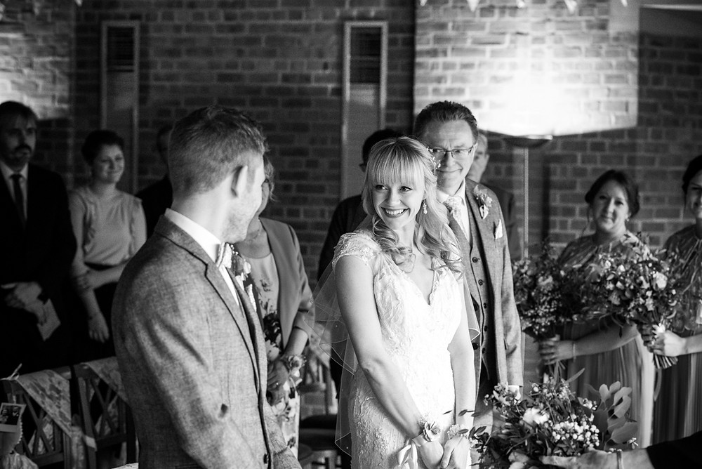 Black and white candid photograph of bride seeing the groom for first time on the day of their wedding at Avoncroft Museum