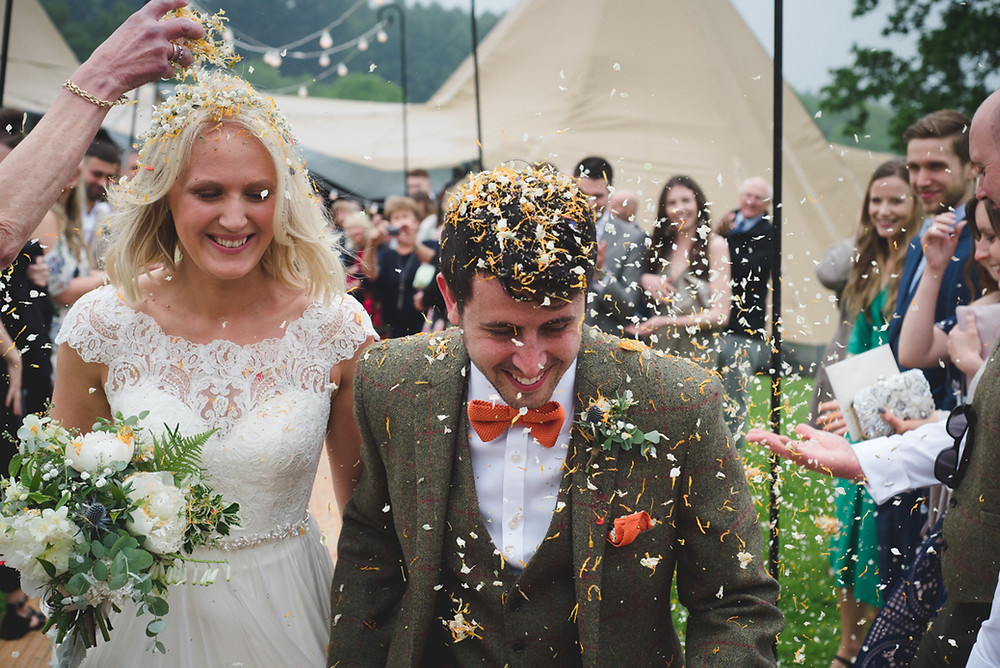 Bride & groom getting confetti thrown on them after their outdoor Ludlow wedding