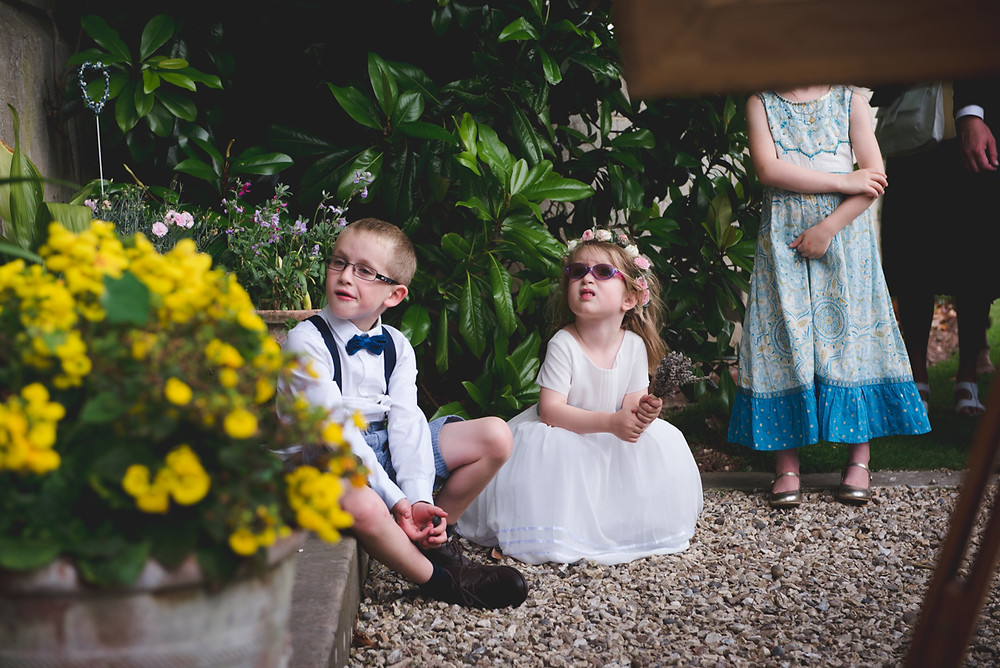 Page Boy and Flower Girl sitting on floor during father of the Grooms speech at Herefordshire wedding reception