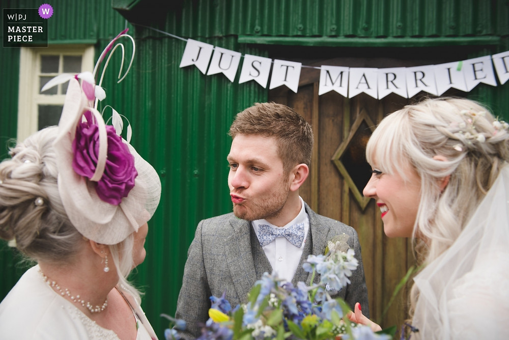 Silly moment of the groom at Avoncroft Museum wedding with lipstick on his lips