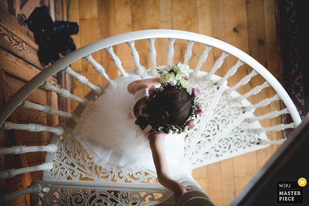 artistic wedding photograph of flower girl descending a spiral staircase