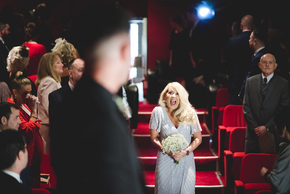 excited looking bridesmaid walking down the cinema aisle at electric cinema wedding