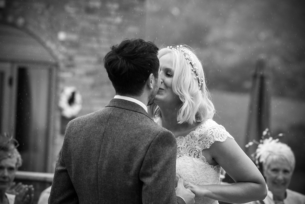 Bride & groom kiss in the rain at Shropshire outdoor wedding