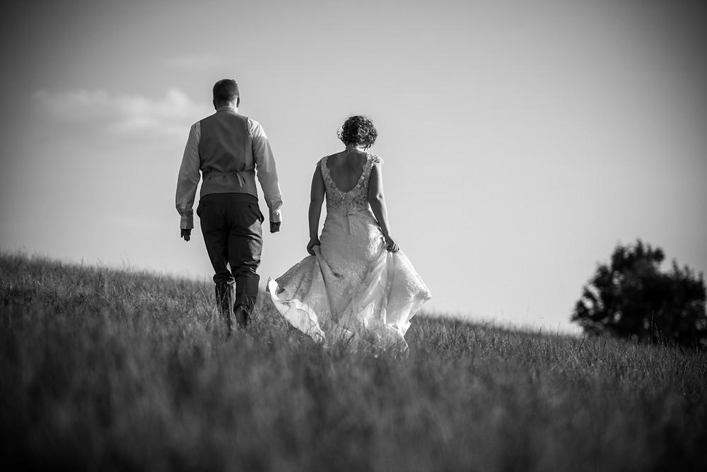 Bride & Groom walking across the hillside at Deer Park Hall Wedding