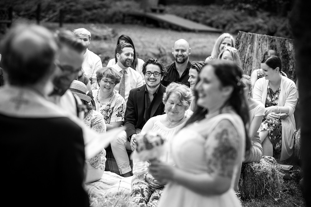 Smiling wedding guest during outdoor wedding - black & white