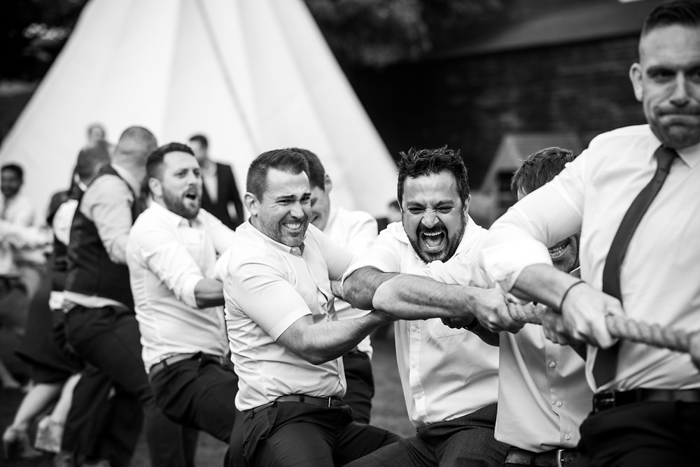 determined wedding guests gritting their teeth in tug of war contest at THe Fleece Inn, Bretforton