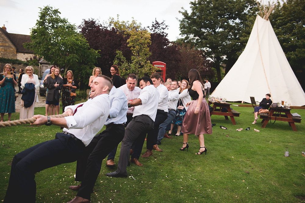 Wedding guests taking part in tug of war at The Fleece Inn near Evesham