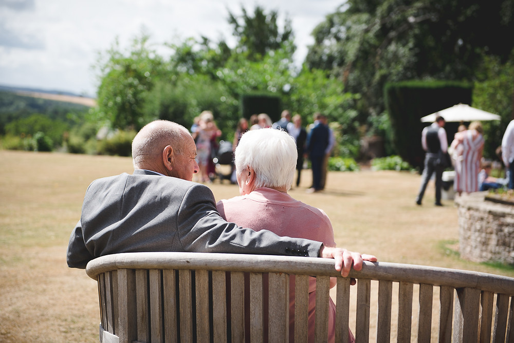 Guests gathering on the lawn at How Caple court before open air wedding ceremony