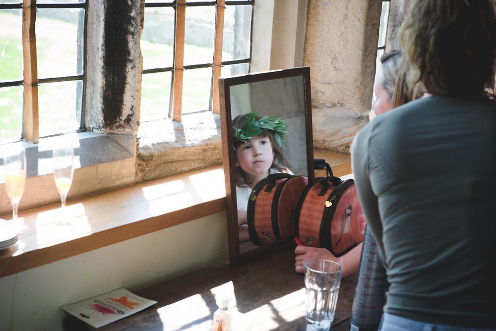 Flowergirl with flower crown looking in mirror