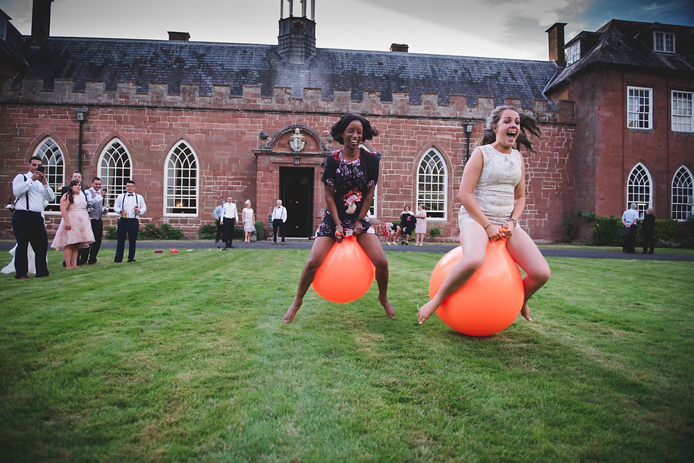 Wedding guests having space hopper race at Hartlebury Castle