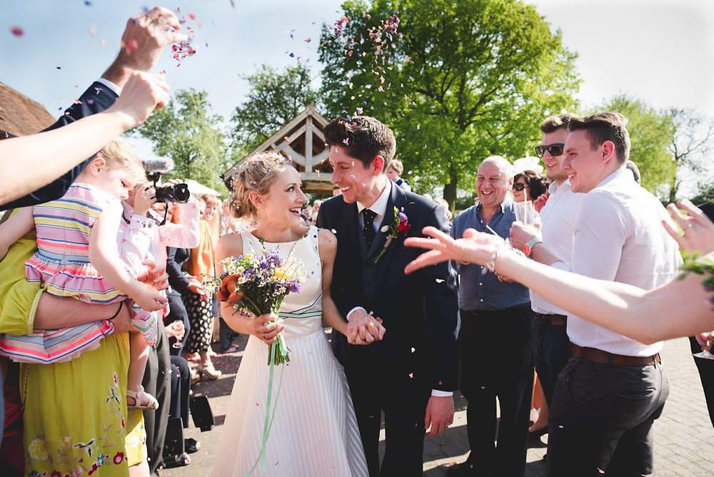 Bride & Groom getting confetti thrown over them at Leamington Spa wedding ceremony