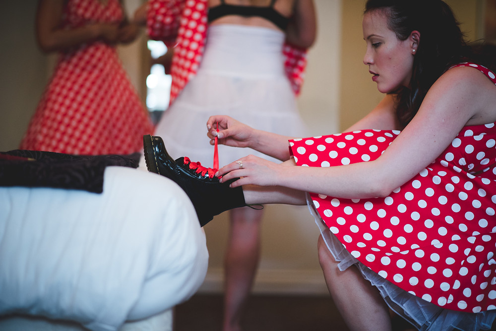 Bridesmaid in red polka dot dress tying up her black Doc Marten boots