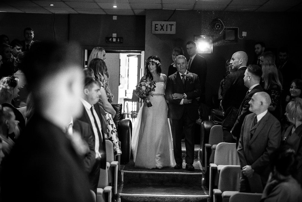 reportage black & white image of bride and her father walking down the aisle at The Electric Cinema in Birmingham