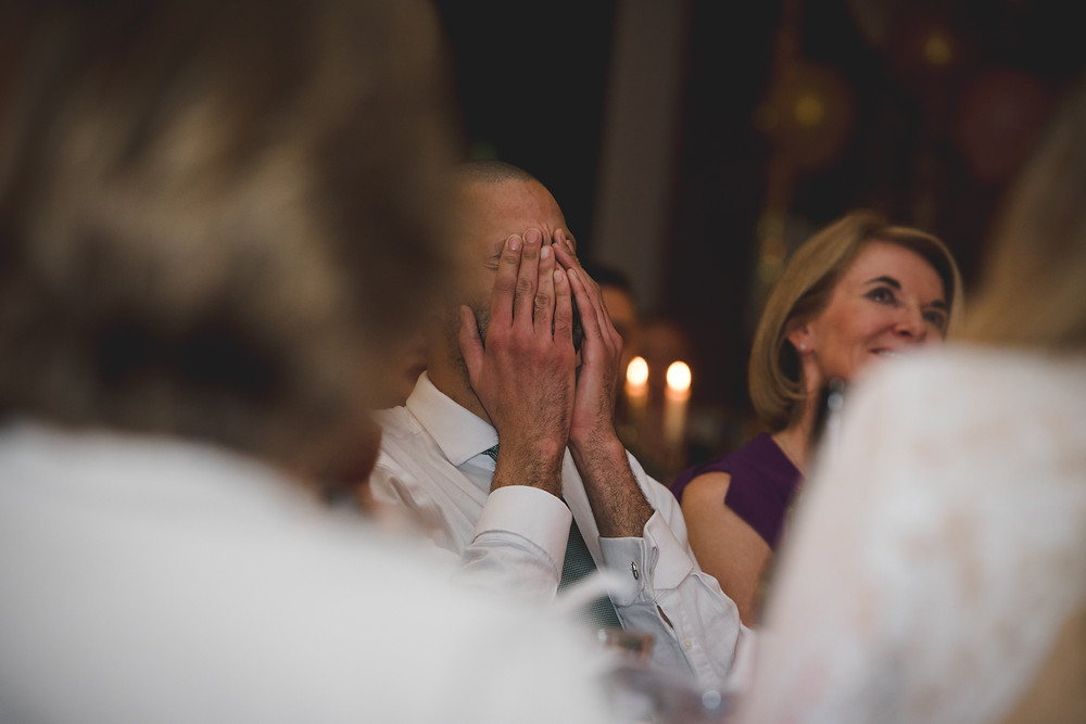 brother of groom with head in his hands during wedding speeches