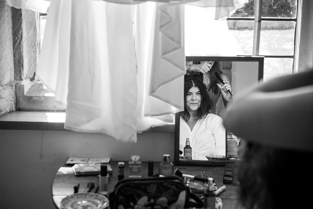 Black & white candid image of bride getting ready at Swarkestone pavilion