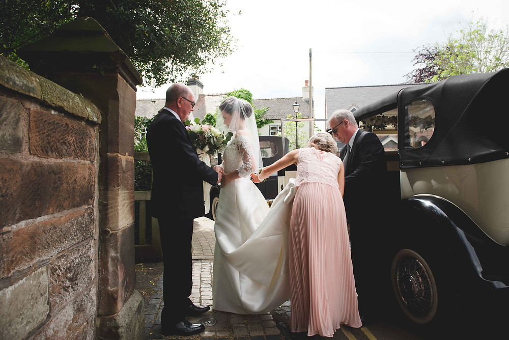 Bride getting out of wedding car in Brewood