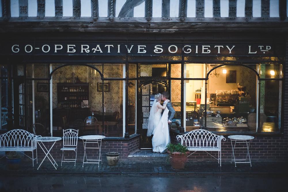 Bride & Groom embracing in doorway of old co-op building at Avoncroft Museum wedding