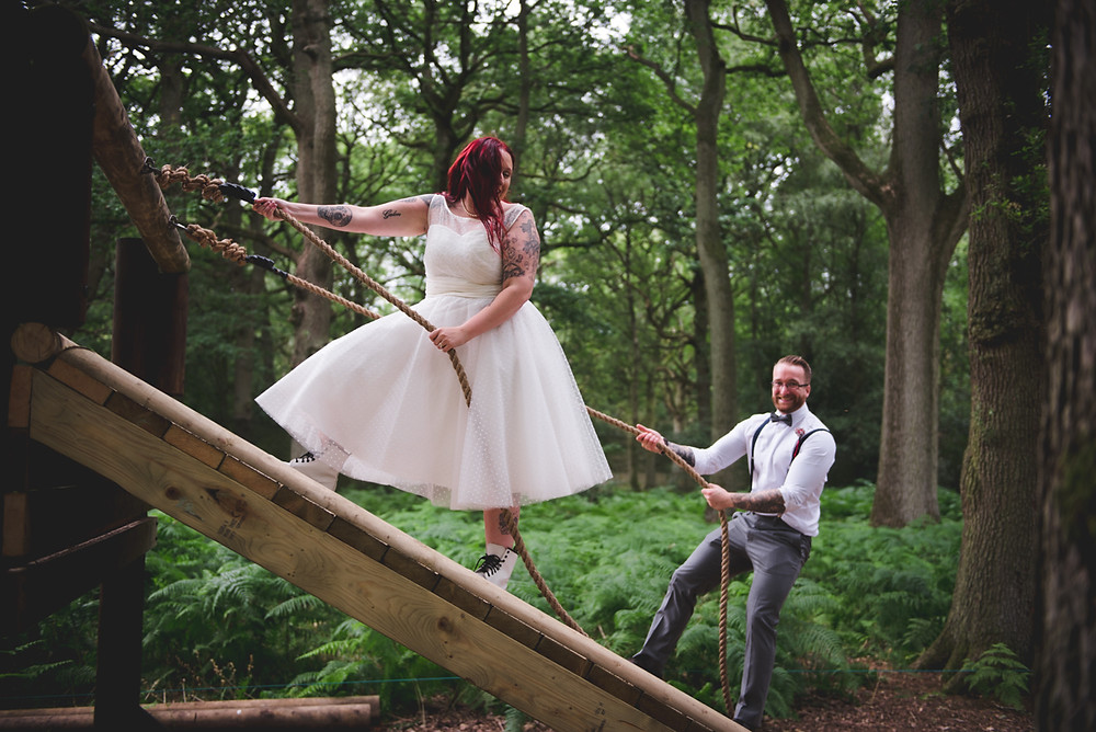 Bride & Groom climbing up ropes at their wedding at umberslade adventure near Solihull