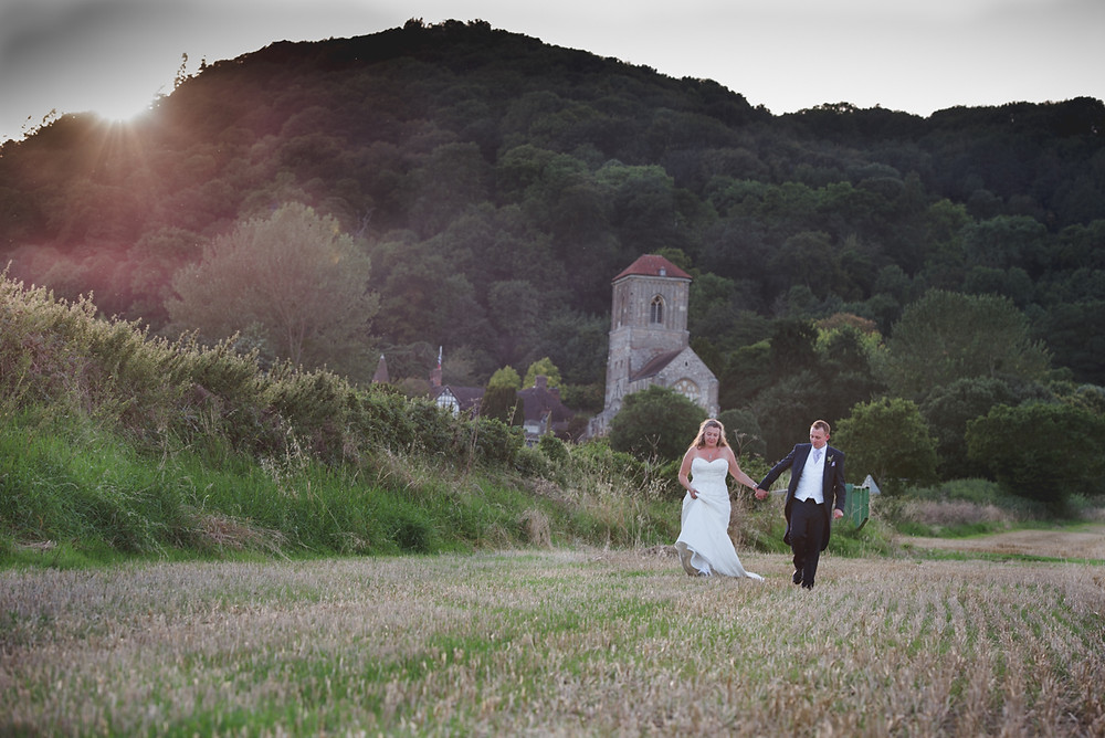 Bride & Groom walking in a field with Malvern Priory in the bakcground