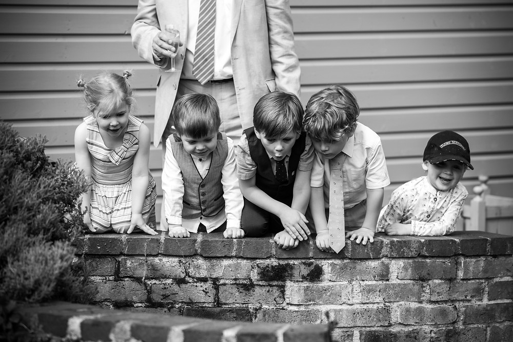 Children looking into fish pond at Warwickshire wedding