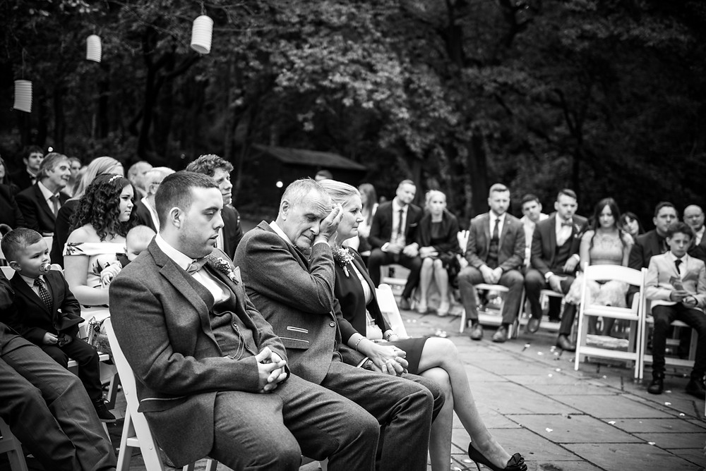 Father of the groom wiping a tear from his eye at outdoor Staffordshire wedding
